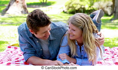 Couple on a picnic tablecloth in a park