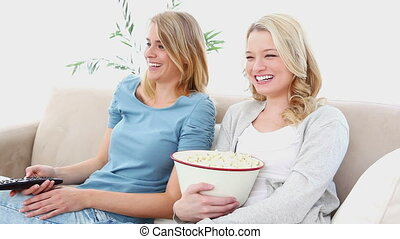 Blonde women watching TV while sitting on a sofa