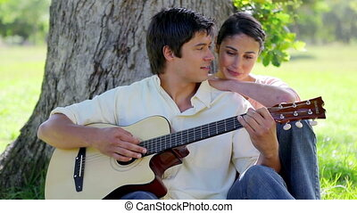 Smiling man playing guitar for his girlfriend