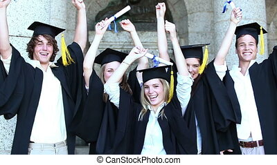 Happy graduates raising arms and jumping while giving...