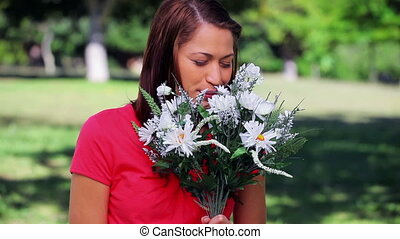 Cheerful woman holding white flowers in a parkland