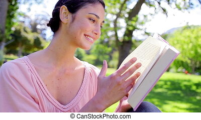 Happy brunette woman reading a novel