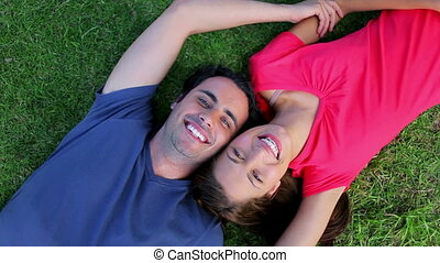 Smiling couple lying on the grass while enjoying the nature