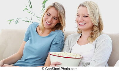 Two friends watching TV with popcorn