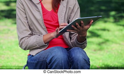 Brunette woman using an ebook in a parkland