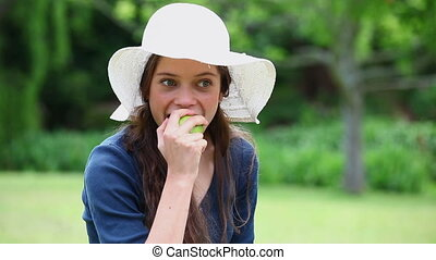 Smiling woman eating an apple in a park