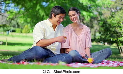 Laughing couple drinking orange juice in a parkland