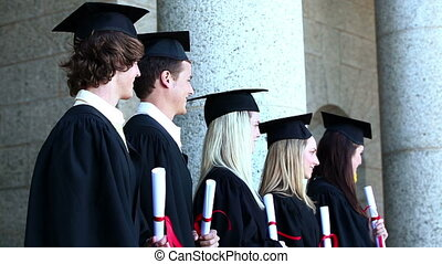 Graduates in line in front of columns
