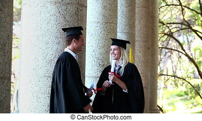 Male graduate comes and gives high-five to friends