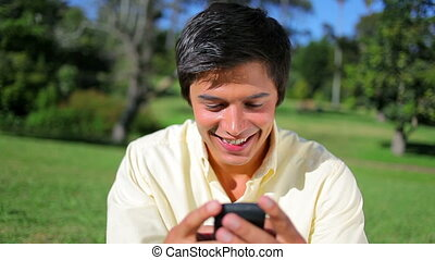 Smiling man texting on his cellphone