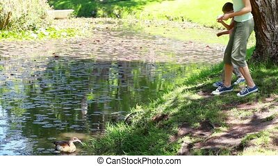 Mother and daughter nourishing ducks in a park