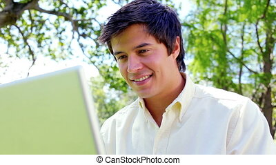 Happy man using his laptop in a parkland