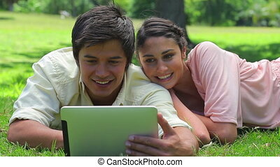 Smiling couple watching a tablet computer in the countryside