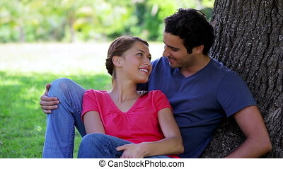 Happy couple hugging while leaning against a tree