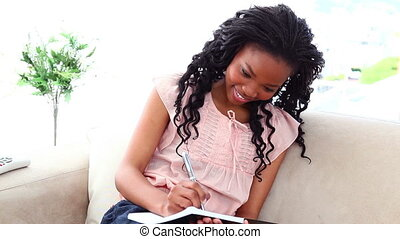 Woman writing on a note pad while sitting on a sofa