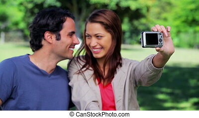Smiling couple taking a picture of themselves in the...