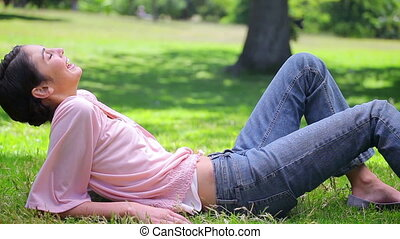 Smiling woman lying on the grass