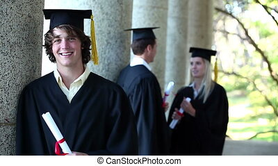Portrait of a male graduate in foreground leaning against...