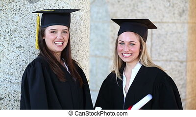 Happy students holding their diplomas in front of the...