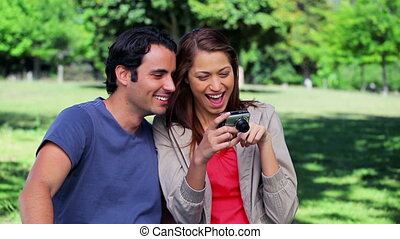 Smiling couple looking at a digital camera