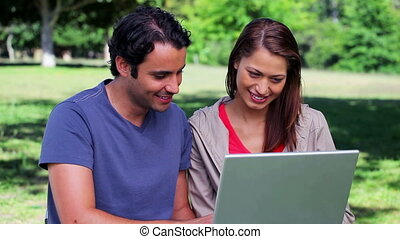 Smiling couple using a laptop together in a parkland