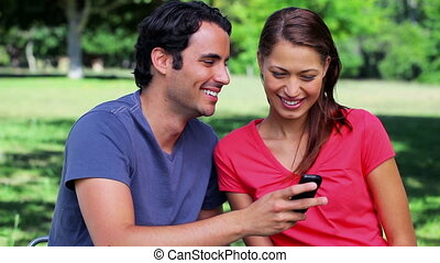 Happy couple looking at a text on a mobile phone