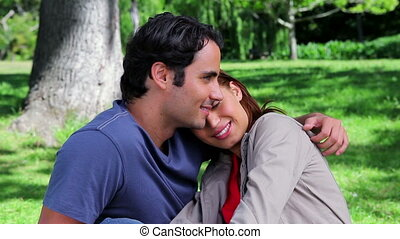 Smiling couple hugging each other while sitting on the grass