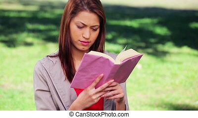 Brunette woman reading an interesting book in the...