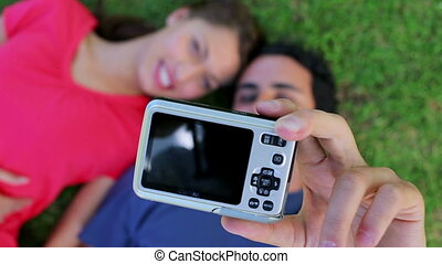 Lovely couple photographing themselves while lying on the...