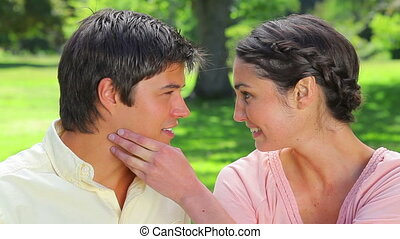 Happy woman placing her hand on her boyfriend in a parkland