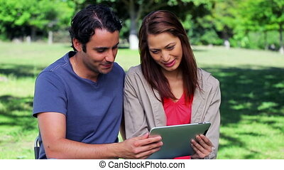 Happy couple holding a tablet pc together in a parkland