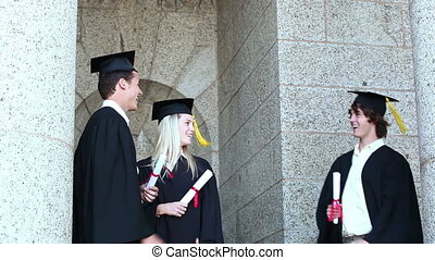 Graduates giving high-five and then posing