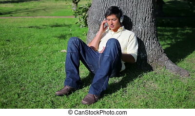 Smiling man listening to music while sitting against a tree