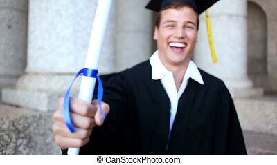 Happy student holding his diploma in front of the university