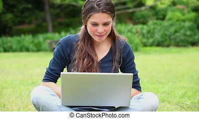 Happy woman typing on her laptop in a park