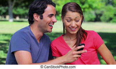 Happy couple receiving a surprising text