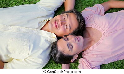 Peaceful couple lying on the grass