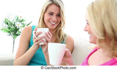 Two blonde friends drinking a coffee together