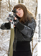 Brunette aiming a gun in the forest