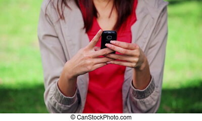 Serious woman sending a text message