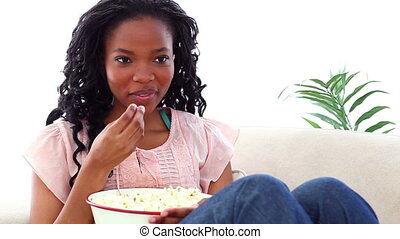 Woman eating popcorn while watching TV on a sofa