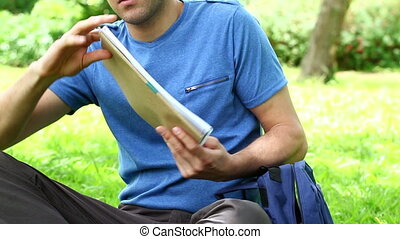 Happy man taking his notebooks in a parkland