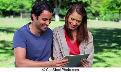 Happy couple looking at a tablet computer in a parkland