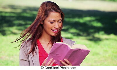 Happy woman reading an interesting novel in the countryside