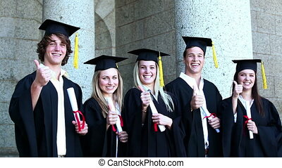 Laughing graduates the thumb-up in front of the university