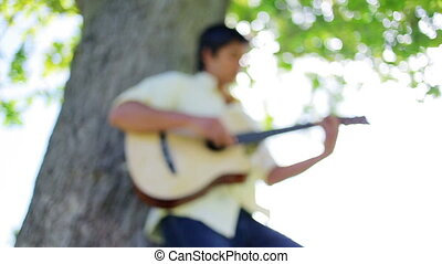 Brunette man playing guitar against a tree in a park