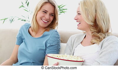 Two blonde watching TV while sitting on a sofa
