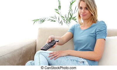 Woman changing of channel while sitting on a sofa