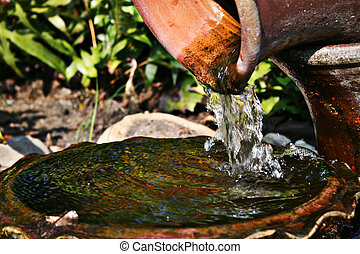 Old jug pouring water  - Old earthenware jug pouring water
