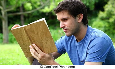 Serious man reading a novel in a park